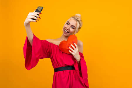 European blond girl in a red dress takes a selfie on the phone and holds a red heart out of paper on an orange studio background with copy space
