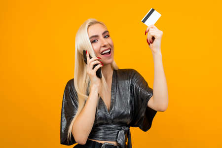 girl holds a phone and a credit card with a mockup on an orange background with copy space 免版税图像