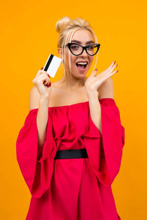 European girl in a red elegant dress with a credit card for shopping in hands with a mockup on a yellow studio background 免版税图像