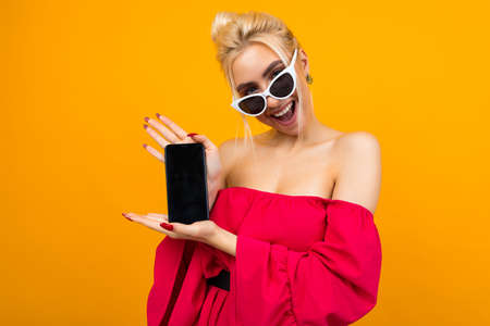 portrait of a smiling european girl with a phone in her hands with a blank for the site on a yellow background