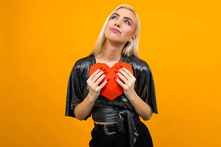 Caucasian blond girl hugs a 3D heart figure on an orange background. Valentines Day