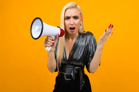 portrait of a caucasian blond girl in a graphite blouse talking news in a megaphone on a yellow studio background
