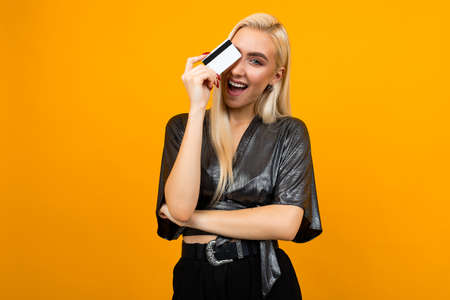 portrait of a sexy european girl holding a card with a mockup for shopping on a yellow background 写真素材