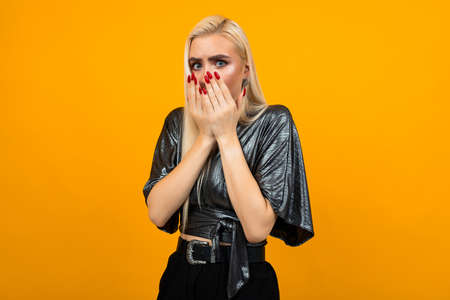 portrait of a blond startled young woman covering her face with hands on a yellow studio background