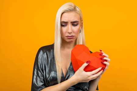sad european young woman holding a red heart in her hands on an orange studio background 写真素材