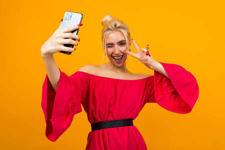 girl in an elegant red dress makes a photo of herself on the phone on a yellow studio background