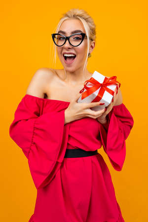 pleasantly surprised attractive lady in a red dress received a white gift box with a red ribbon for a birthday on an orange background