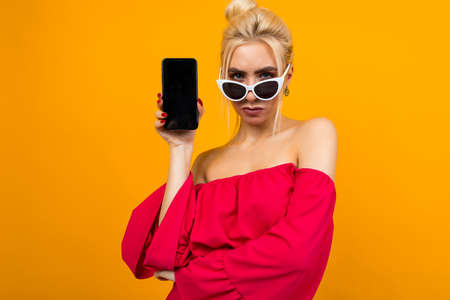 serious lady shows a blank phone screen with a mockup on an orange background