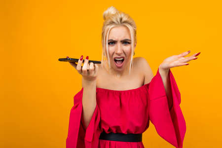 European girl in a red dress indignantly speaks on the phone on an orange isolated background 免版税图像