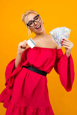 happy girl in a red dress with a bunch of money and a credit card with a mockup on a studio background