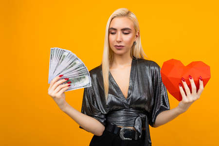 European blonde girl received a cash gift and holds a paper heart in his hands for Valentines Day 免版税图像