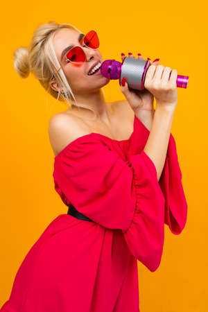 girl in a red elegant dress with bare shoulders with retro glasses holds a microphone and sings