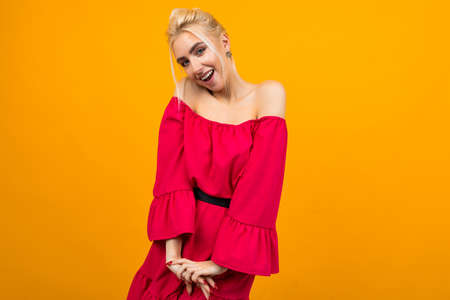 sexy smiling blonde girl in a red dress posing for advertising on a yellow studio background