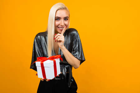 European girl holds a box with a gift and tells a secret on an isolated yellow background with copy space