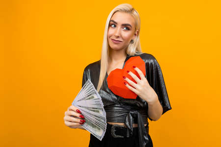 European blonde girl received a cash gift and holds a paper heart in his hands for Valentines Day Stock Photo