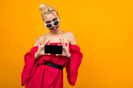 Caucasian charming girl in a red dress shows a blank phone screen with mockup for the site on a yellow background 免版税图像 - 152725884