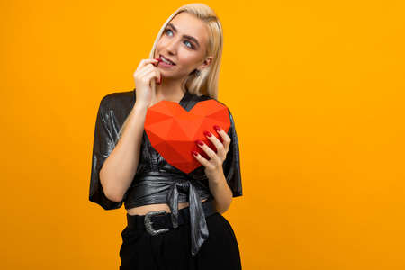 European attractive girl hugs a 3D heart figure on an orange studio background. Valentines Day