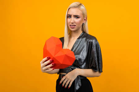 portrait of a sad distressed european young woman holding a red heart in her hands on an orange studio background Stock Photo