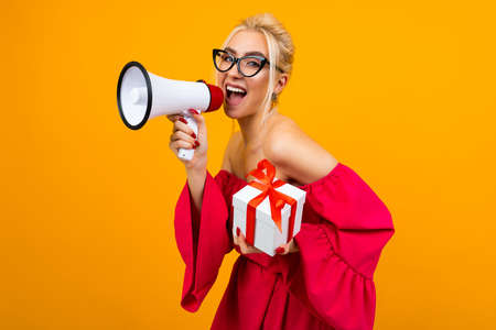 blond girl in a red dress talks about a draw with a megaphone and a gift box in hands on a yellow background