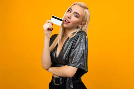 attractive blonde girl in a shiny blouse holds a credit card with a mock up for a bank on an isolated orange studio background with copy space Stock Photo