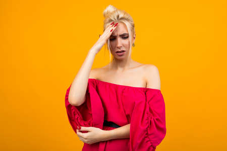 sexy excited blonde girl in a red dress on a yellow studio background Stock Photo