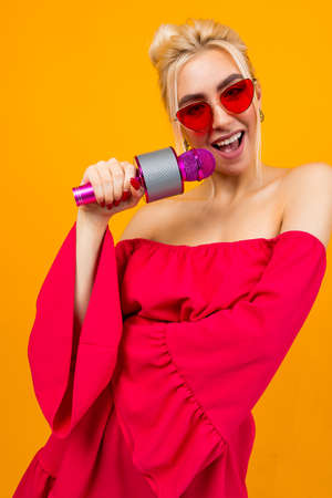 Sexy girl in a red dress celebrates a birthday and sings in karaoke Stock Photo