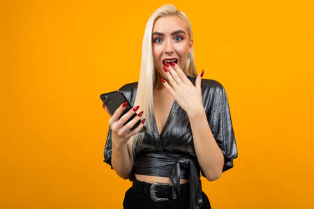 European stylish charming girl in surprise reads messages on her smartphone on a yellow studio background Stock Photo
