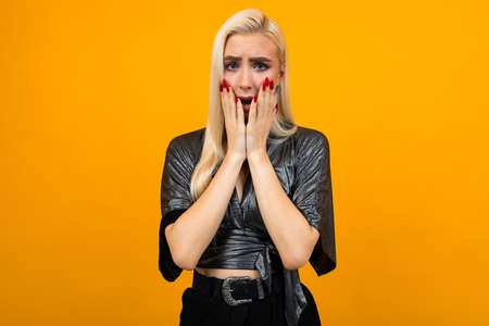 portrait of a blond young woman showing anxiety emotions on a yellow studio background