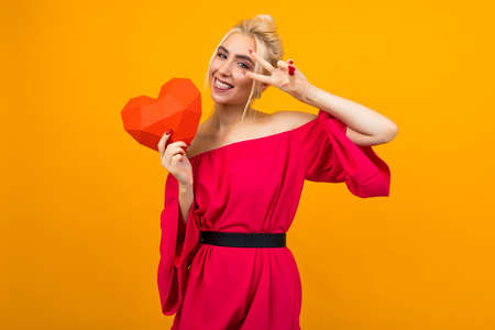happy joyful smiling blonde girl in red dress holds red paper heart for valentines day