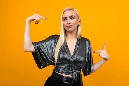 Confident blond young woman shows her hands on herself on a yellow background with copy space