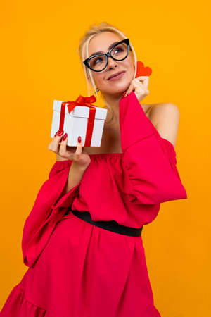 European girl in a red dress holds a gift and a red heart on an orange studio background