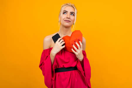 European blond girl in a red dress holds a phone with a dating site and holds a heart made of paper Banco de Imagens - 153643431