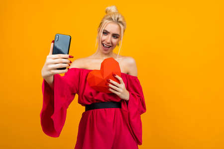 European blond girl in a red dress makes selfie on the phone with a red heart made of paper on an orange studio background Banco de Imagens - 153643433