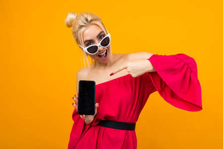 blond emotionally cheerful smiling girl shows a blank phone screen with a mockup on an orange background Banco de Imagens - 153658749