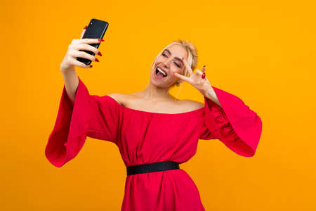 young smiling woman in an elegant red dress makes a photo of herself on the phone on a yellow studio background