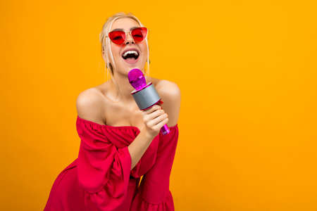 bright girl in a red dress with bare shoulders sings with a microphone Banco de Imagens - 153658760