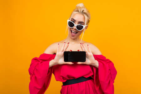 European girl shows a phone screen with a blank for the site on a yellow background