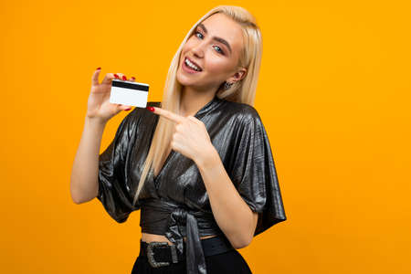 portrait of a sexy european girl holding a card with a mockup for shopping on a yellow background Banco de Imagens - 153658768
