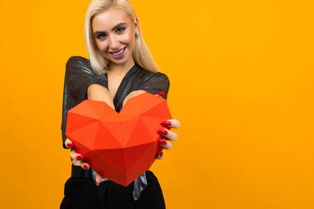 cute blond girl holds out a 3D heart figure on a yellow background with copy space Banco de Imagens - 153658769