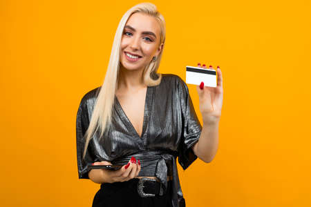girl holds a phone and a credit card with a mockup on an orange background with copy space Banco de Imagens