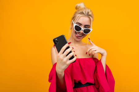 charming lady in a red dress in sunglasses on her face holds a phone on a yellow background with copy space Banco de Imagens - 153584761