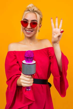 European elegant girl in a red dress with bare shoulders, with retro glasses, holds a microphone in her hands and sings Banco de Imagens - 153643435