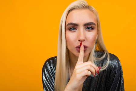portrait of a blond young woman asking to be quieter on a yellow studio background Banco de Imagens - 153643437