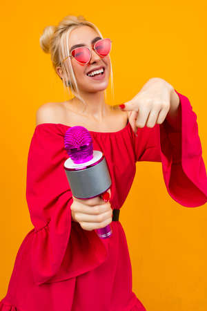 Sexy girl in a red dress celebrates a birthday and sings in karaoke Banco de Imagens