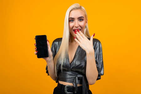 portrait of a surprised young girl with a phone in her hands with a mockup on a yellow background Banco de Imagens - 153643440