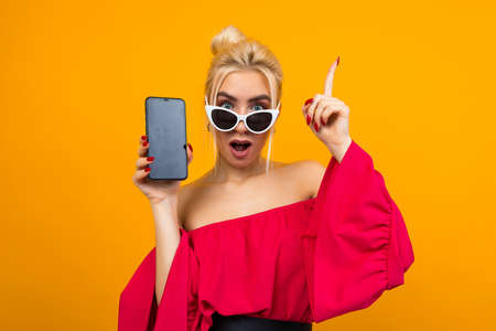 surprised lady in a red dress shows a blank smartphone display with a layout on an orange background with copy space