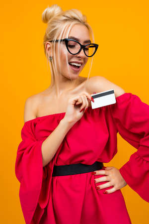 attractive girl in a red dress holds a credit card with a layout for the bank on a yellow background Banco de Imagens - 153643442