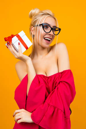 surprised attractive girl in a red dress holds a white gift box with a red ribbon for Valentines day on an orange background Banco de Imagens - 153584847