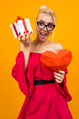 European girl in a red dress holds a gift and a red heart on an orange studio background Banco de Imagens - 153584948