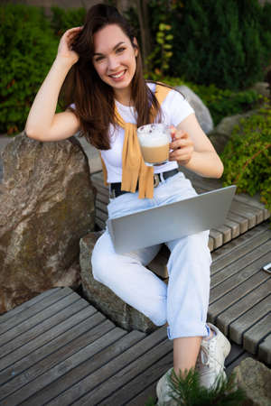 cute young female student sitting with laptop on lunch break sitting outside.